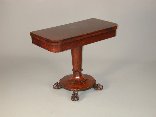 A William IV rosewood card table, the fold over top on central support terminating on circular base and lion paw feet 92 cm wide 45 cm deep x 76 cm high