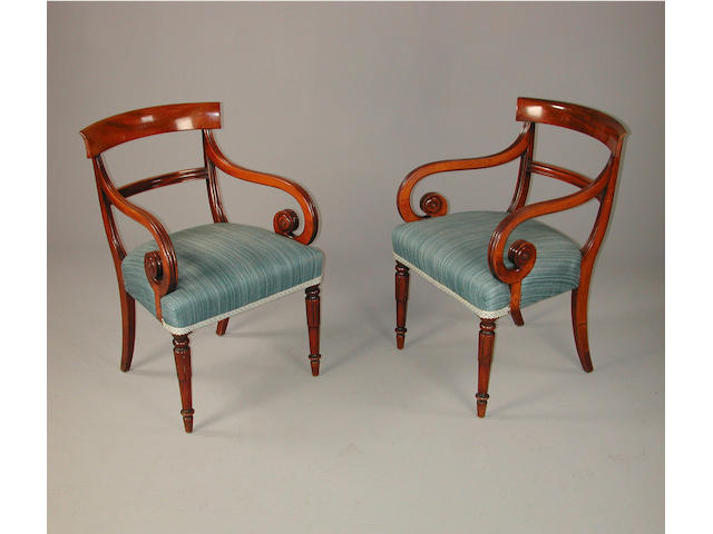 A pair of late Regency mahogany open arm chairs, with over stuffed seats on lappet carved frontlegs
