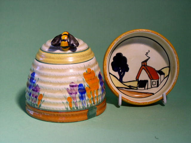 A Clarice Cliff 'Crocus' beehive preserve pot and cover and a 'House and Bridge' pin tray