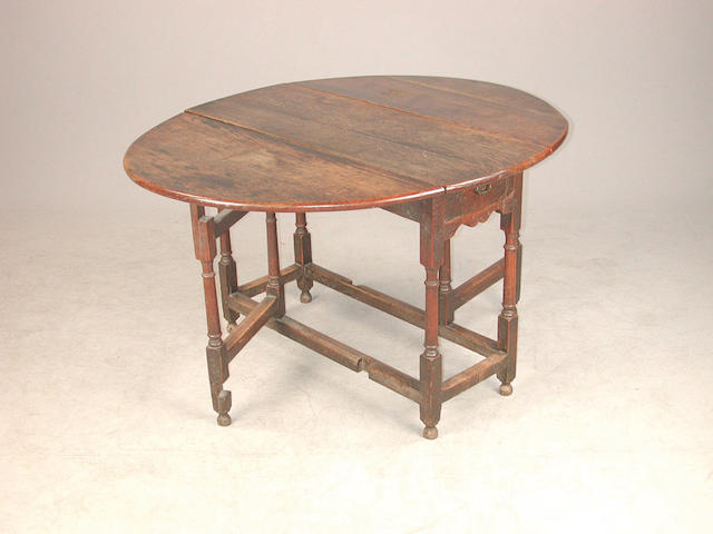 An 18th century oak oval gateleg table with frieze drawer, 126 cm wide, 106 cm deep, 71 cm high.
