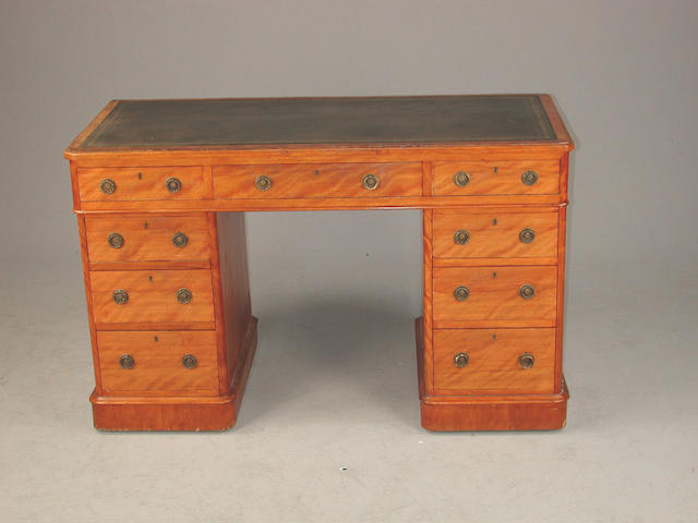 A Victorian satinwood pedestal desk, with inset faux leather top over nine graduated drawers grouped around a kneehole replaced faux...