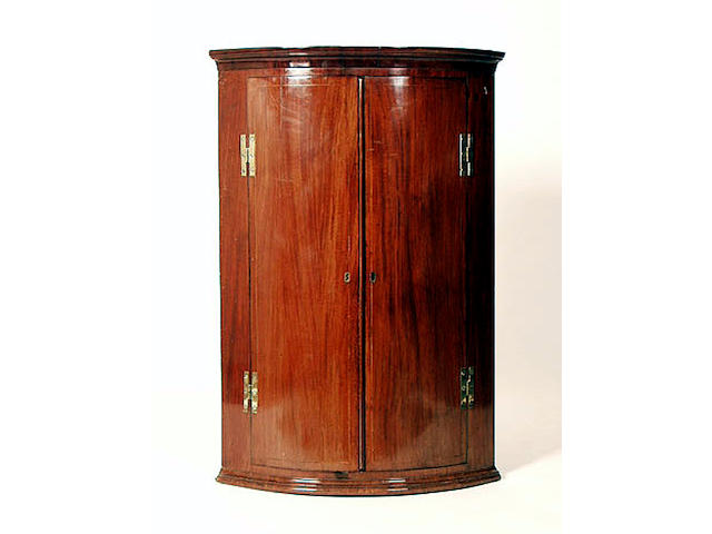 A George III mahogany wall mounted corner cabinet, 71cm wide.