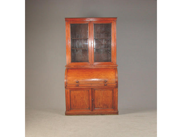A Victorian mahogany cylinder bureau bookcase, with glazed doors revealing ajustable shelves, the cylinda enclosing drawers, pigeion...