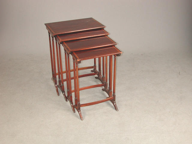 An Edwardian nest of four mahogany tables, the rectangular tops with satinwood and boxwood banding one stretcher detached, some legs...