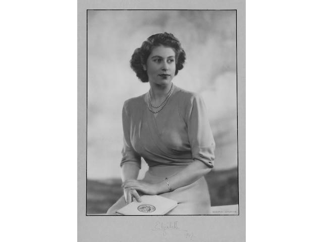 Gallantry Groups, Dorothy Wilding, portrait photograph of Princess Elizabeth showing her seated and holding book, signed Elizabeth 1947. Framed and glazed with slight foxing to mount (image 294 x 208mm).
