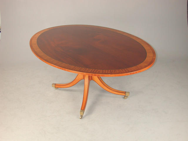 A reproduction mahogany and satin wood crossbanded oval breakfast table