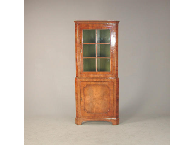 A 20th Century walnut corner cabinet, the top section with astragal grazed doors, revealing 83cm x 54cm x 199cm