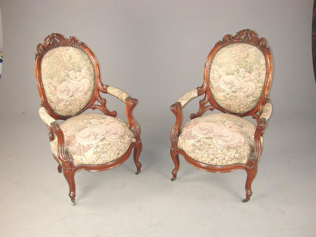 A pair of late Victorian carved mahogany armchairs, with tapestry upholstery, on cabriole legs The tapestry coverings depicting 'The Swing' by Fragonard (1776)