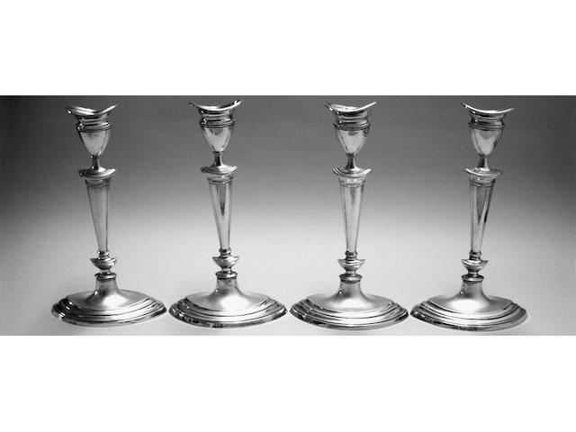 A set of four Edwardian silver candlesticks