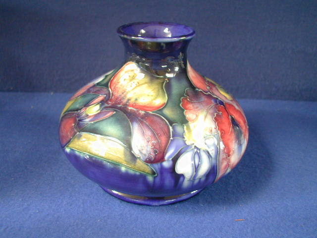 A Moorcroft squat vase, with a navy ground and floral decoration, 14cm high.