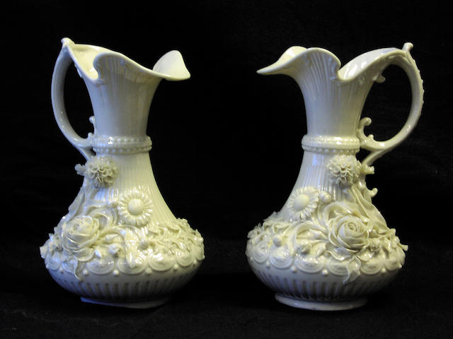 A pair of Belleck white glazed jugs,
