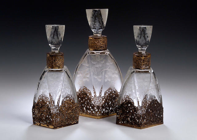 A set of three French silver gilt mounted liqueur decanters, French control marks and London import marks for 1929/1930,