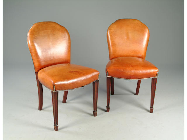 A set of twelve mahogany framed and hide upholstered dining chairs