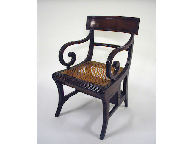 A Regency mahogany metamorphic library chair with a reeded bar back and scroll amrs above a cane panel seat on sabre legs.