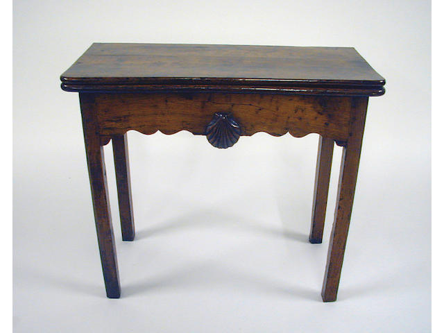 A late 18th Century fruitwood foldover card table, with counter wells to the interior and shell ornament to frieze, probably French, 83.5cm wide.