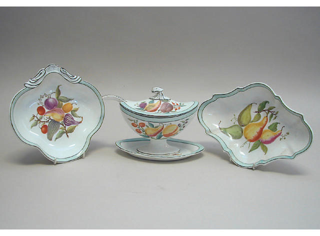 An early 19th Century dessert service, painted in colours with fruit and vegetables within pale blue washed bands and pierced borders, comprising a pair of pierced tureens and stands, a set of four kidney shaped dessert dishes, four shaped oval dessert dishes, oval comport, a pair of tureens, covers and ladles, with one stand and fourteen plates.