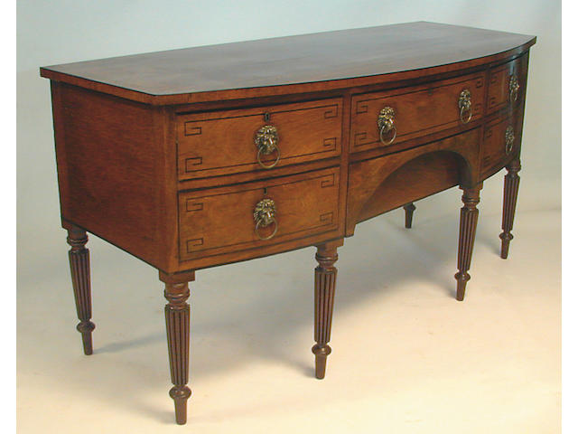 A Regency mahogany bowfront sideboard, with ebony line inlay with two central drawers and two drawers to one side anda  deep cellarette drawer to the other, with lion mask ring handles, on turned reeded tapering legs, 184cm wide.