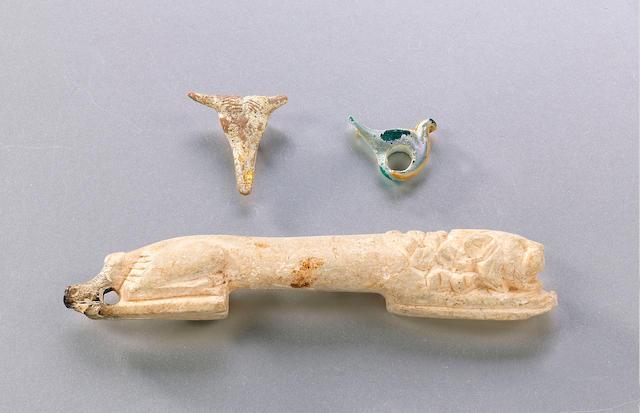 An Eastern Mediterranean recumbent bone lion, a Tarentine terracotta bull's head pendant and a miniature glass bird, Various Periods (3)
