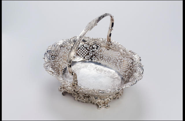 A George II shaped oval swing-handled cake basket by John Hugh Le Sage, 1741,