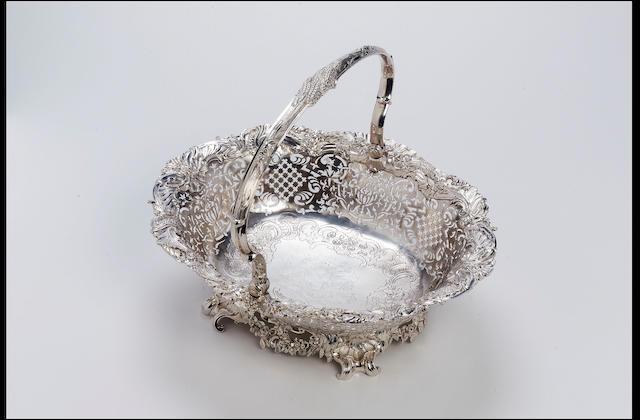 A George II shaped oval swing-handled cake basket by John Hugh Le Sage, 1741,