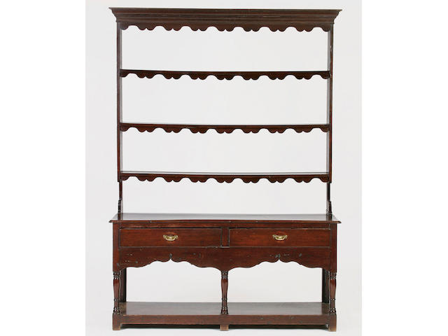 An early 19th Century oak dresser with later open three shelf rack,