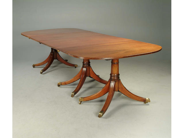 A George III style mahogany triple pedestal D end dining table