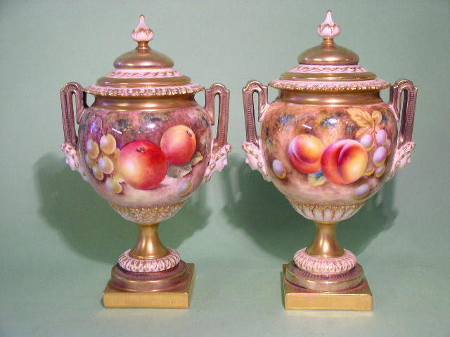 A good pair of Royal Worcester fruit painted vases and covers,