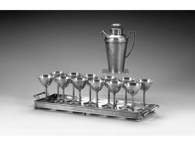 An American Art Deco Cartier cocktail service, the cocktail shaker with twelve goblets and a two-handled tray, marked Cartier, Sterling, impressed patented Dec. 28 1915,