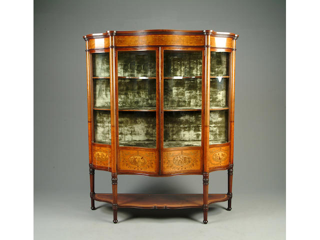 A Victorian satinwood, tulipwood and marquetry inlaid serpentine display cabinet