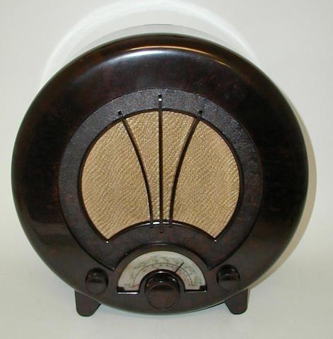 An Ecko Model AD75 circular brown bakelite radio,