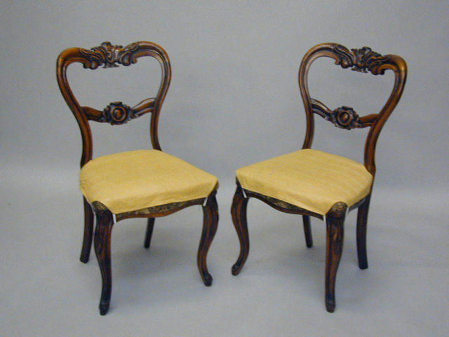 A set of six early Victorian carved rosewood balloon back dining chairs,