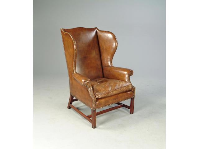 A George III mahogany framed wingback armchair