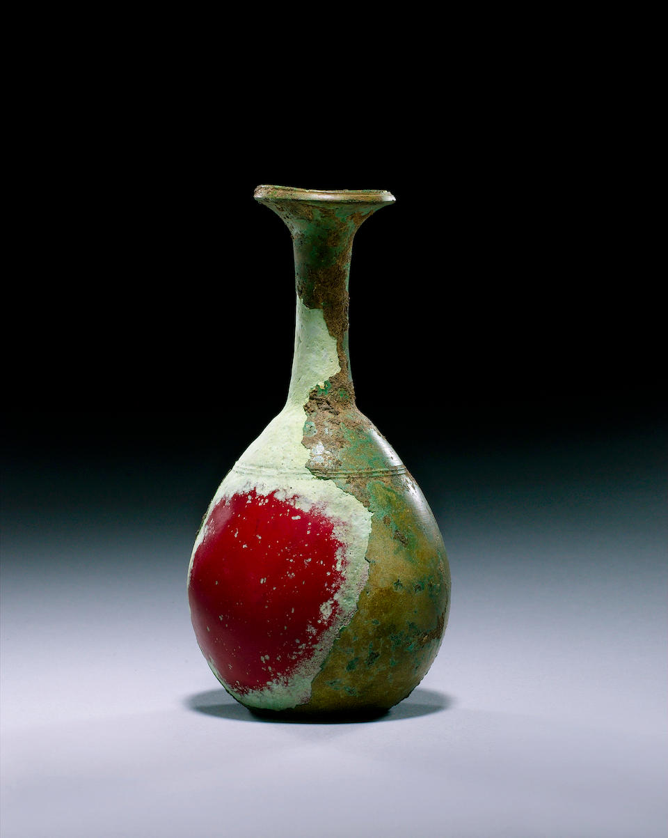 A Hellenistic opaque dark red glass bottle