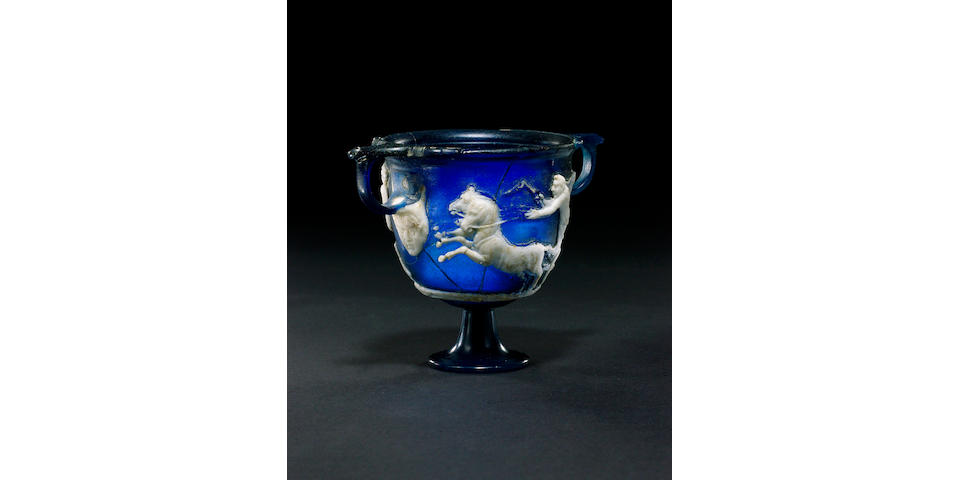 A highly important Roman dark blue cameo carved glass skyphos