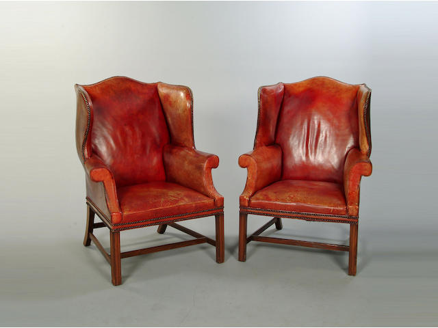 A pair of George III style mahogany framed wing back armchairs