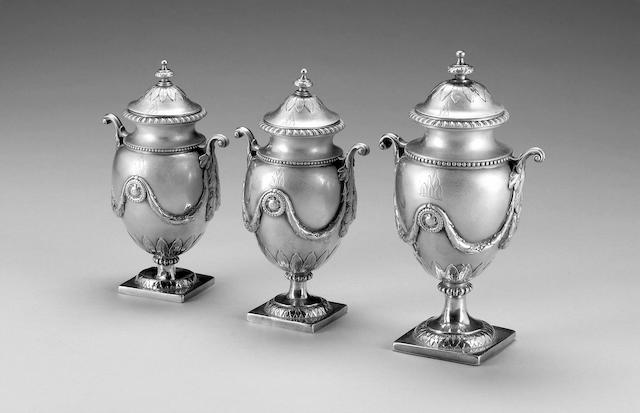 A George III suite of three silver tea caddies, by Andrew Fogelberg, large urn London 1772, one smaller London 1771, the second smaller apparently unmarked, all covers part marked with maker's mark and lion passant,