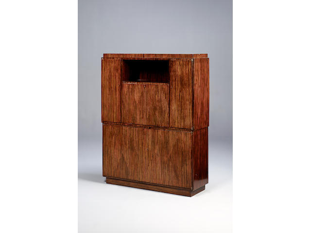 A Macassar ebony parquetry side cabinet with a central fall front compartment designed by Ruhlmann