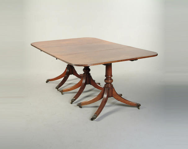 A George style mahogany triple pedestal dining table