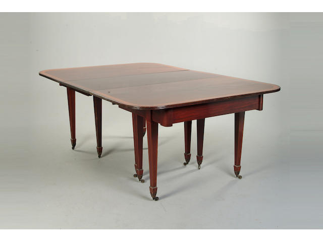 An Edwardian mahogany and satinwood banded extending dining table