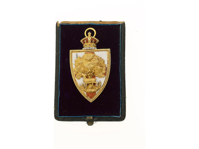 """City of London, a gold and enamel pendant (58mm x 34mm), the obverse in the form of a shield with white enamel and red cross, with sword in top left corner, attached to the front a stag below a tree, the shield surmounted by a Queen's Crown, rev. fitted with pin back and loop at the top, additionally engraved """"CH"""". Contained in Howell James and Co box of issue."""