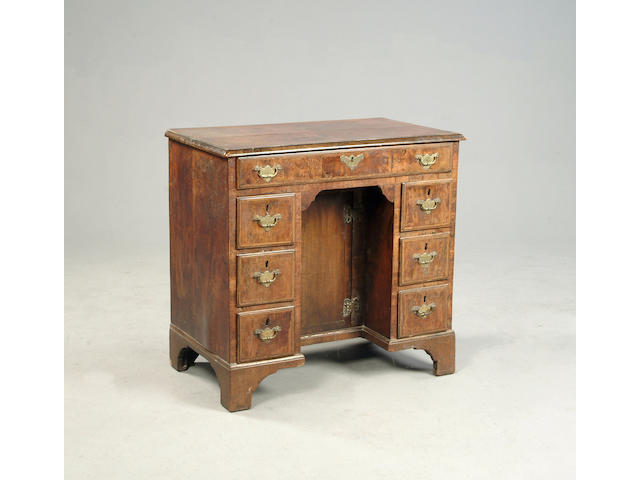 An early 18th century walnut and feather banded kneehole desk