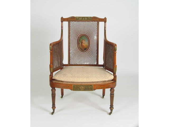 An Edwardian satinwood and cane bergere armchair