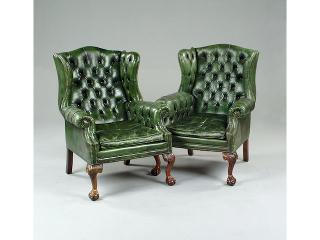 A pair of George III style leather upholstered wingback armchairs