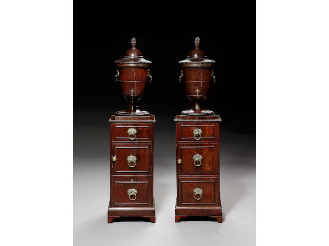 A pair of George III carved mahogany Urns on pedestals,attributed to Gillow,
