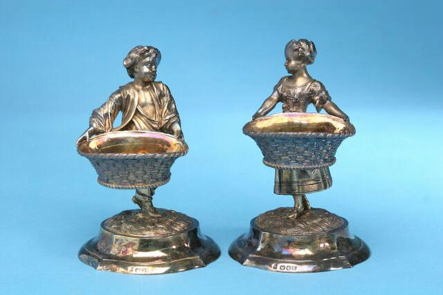 A pair of Victorian figural salts, by Alfred Benson and Henry Hugh Webb, London 1893, inscribed Hunt and Roskell, late Storr and Mortimer and numbered 939,