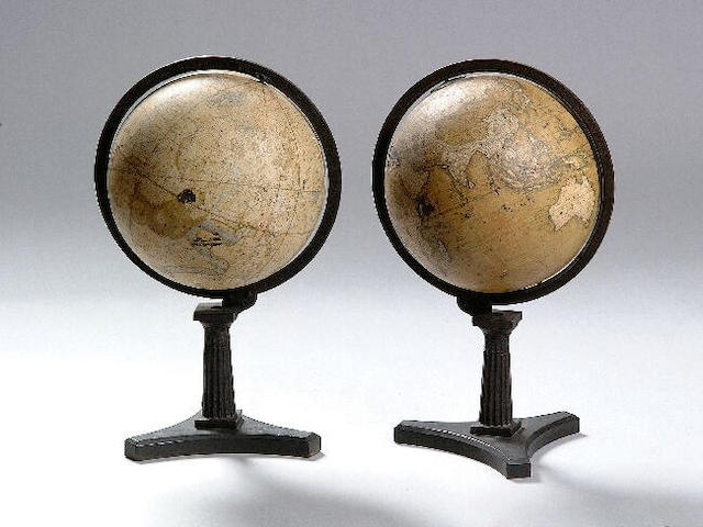 A pair of globes, Terrestrial and Celestial; (Newtons) New and Improved 1847 approximately 32cm diameter, on cast iron table stands with fluted doric columns. (2)