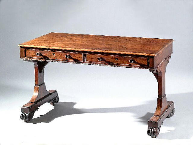 A George IV rosewood library table, the frieze with a pair of cockbeaded drawers and conforming dummy drawers and with applied ribbed moulding, on shaped end supports with anthemion and scroll spandrels and matching feet, 123cm long, the locks stamped Turners W Hampton patent beneath crowns.