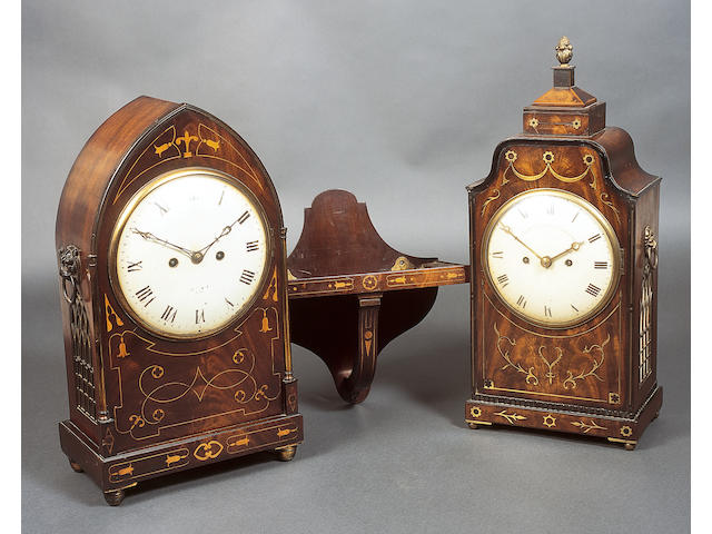 "A Regency figured mahogany, cut brass and line inlaid bracket clock, the painted and domed circular dial inscribed ""French Royal Exchange, London"", within floret, leaf scroll and line inlays, below an arched moulded edge top and raised finial, Gothic arch brass grille sides, each below a lion's mask handle, on a conforming inlaid plinth base and ball feet, twin fusee eight day striking movement, 54.5cm high, together with a patinated mahogany bracket, 52cm high.  (2)  See illustration of clock"