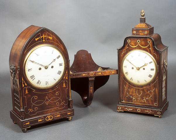 """A Regency figured mahogany, cut brass and line inlaid bracket clock, the painted and domed circular dial inscribed """"French Royal Exchange, London"""", within floret, leaf scroll and line inlays, below an arched moulded edge top and raised finial, Gothic arch brass grille sides, each below a lion's mask handle, on a conforming inlaid plinth base and ball feet, twin fusee eight day striking movement, 54.5cm high, together with a patinated mahogany bracket, 52cm high.  (2)  See illustration of clock"""