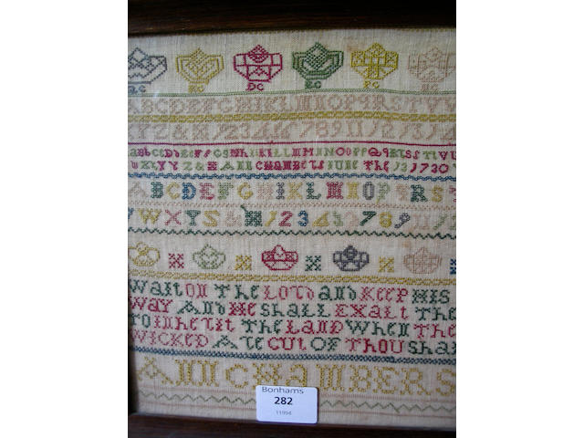 A George II sampler colourfully worked in silk threads to linen ground,
